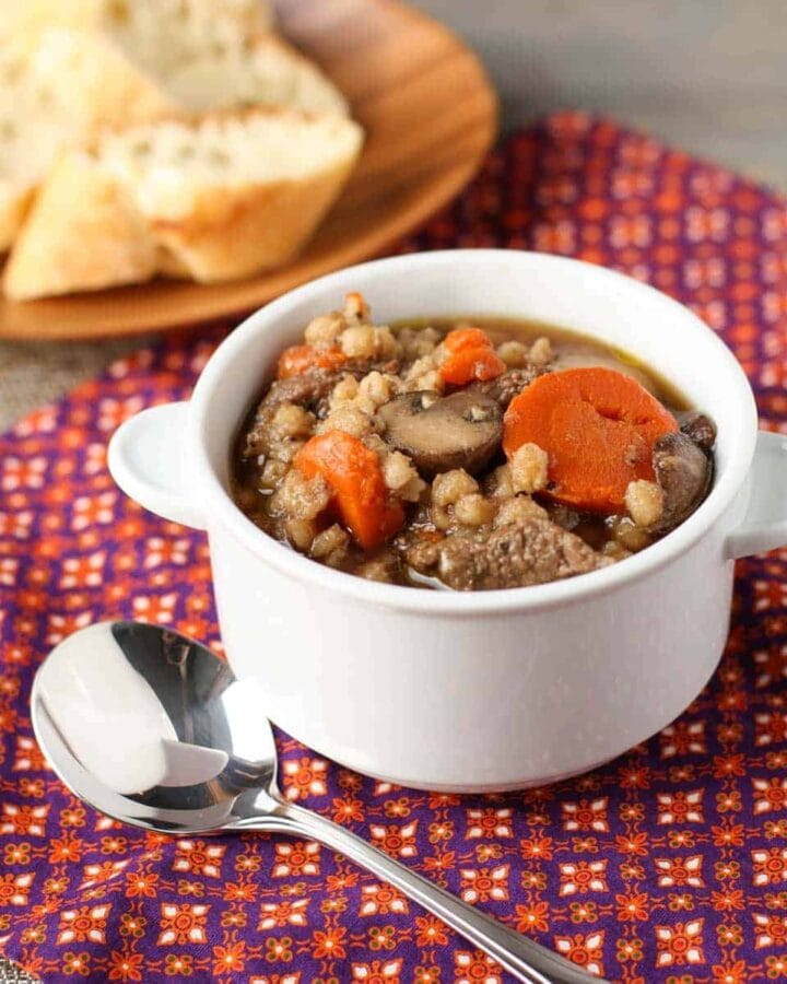 A bowl of beef and barley soup with spoons.