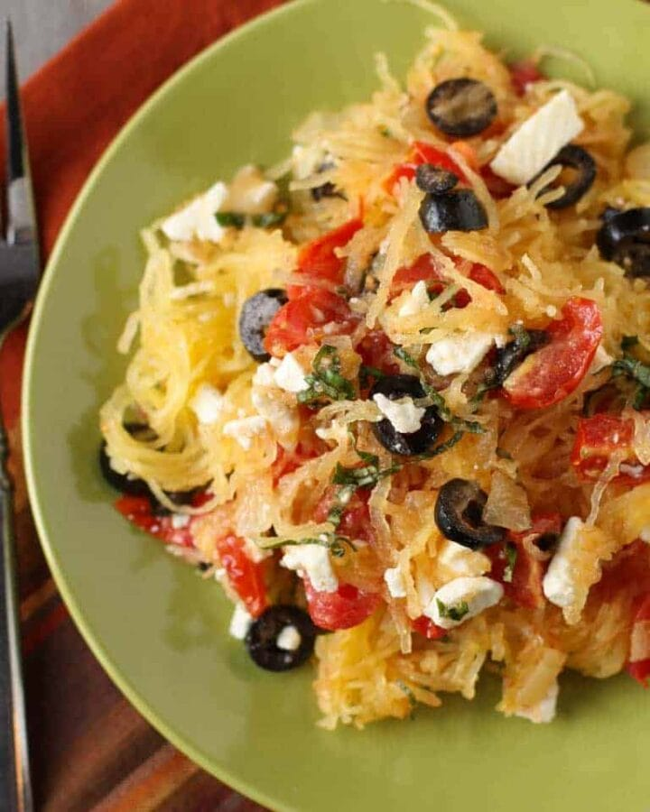 A plate of spaghetti squash on plate with olives and cheese.
