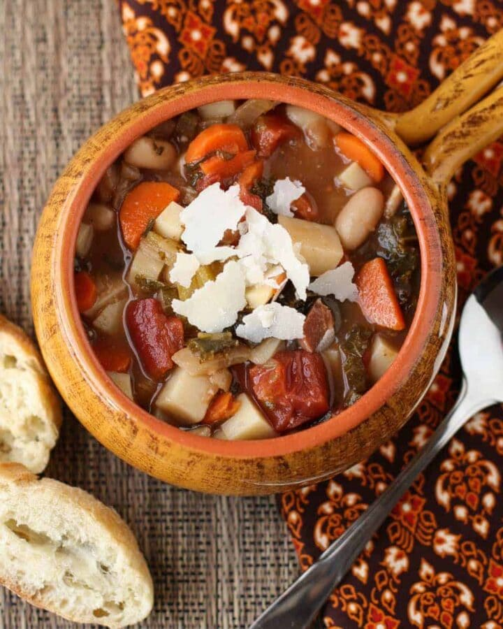 A bowl of winter minestrone soup with bread.