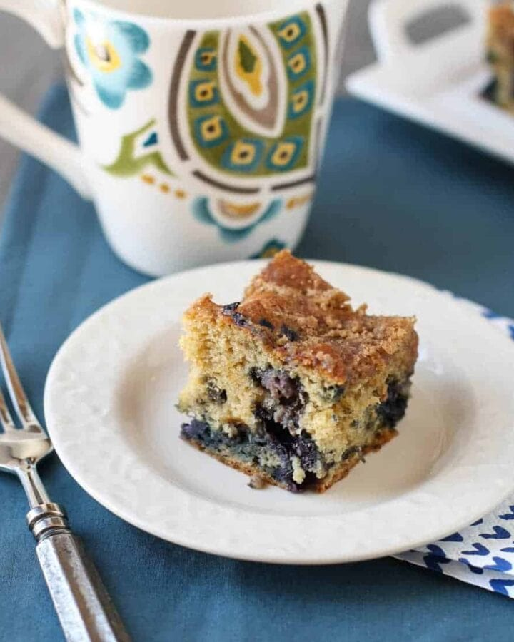 A piece of cake on a plate, with Blueberry.