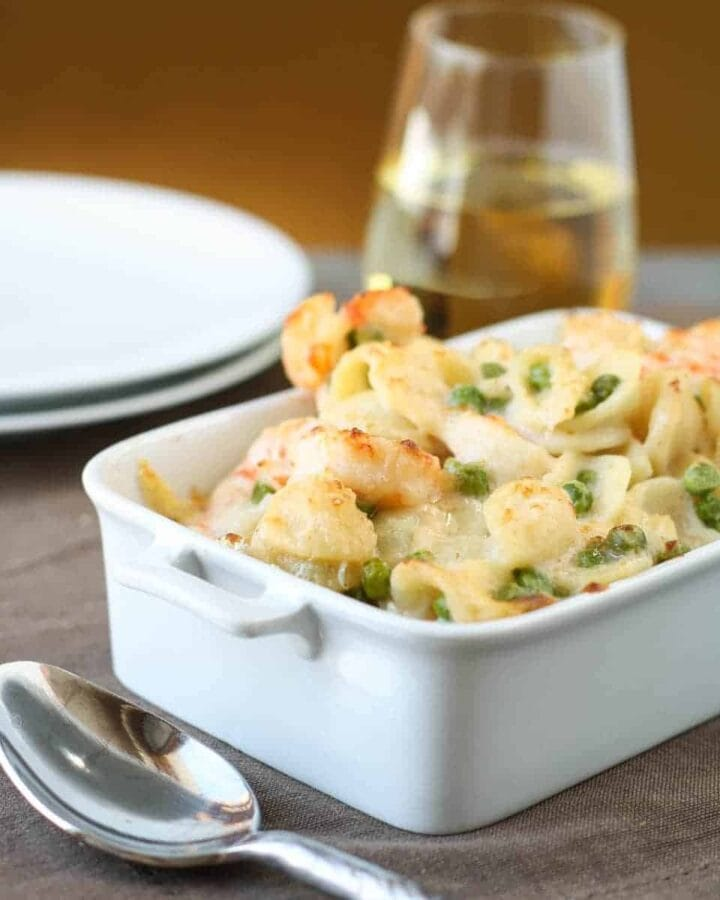 shrimp and pea pasta in white dish on a table.
