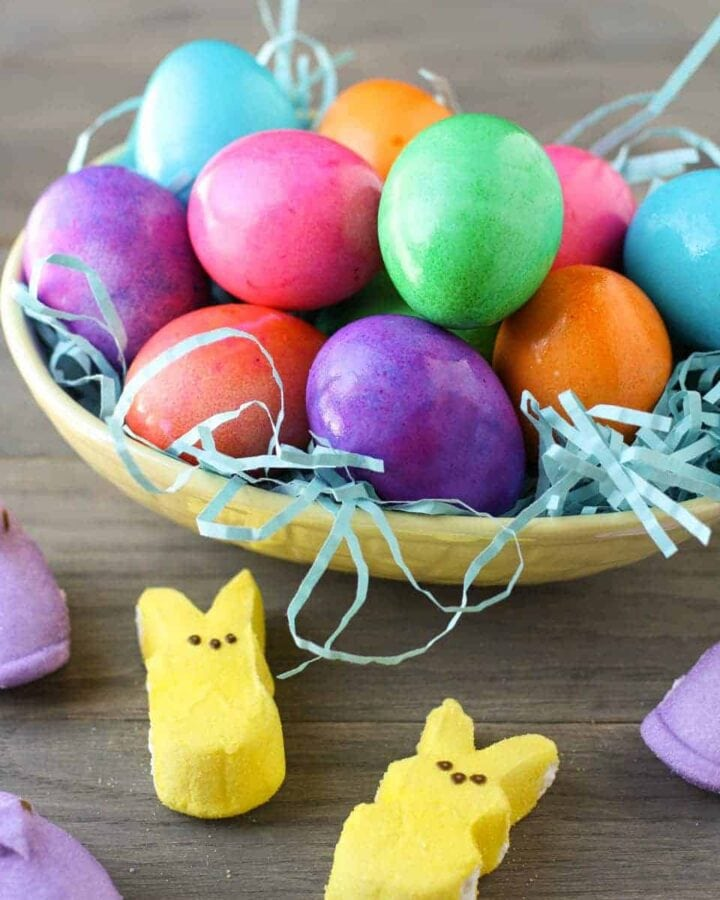 colored eggs in bowl with peeps.