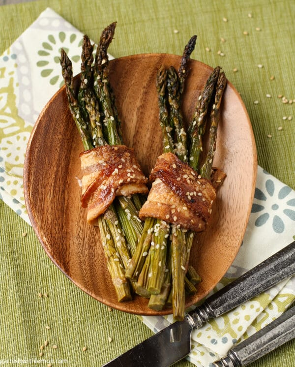 Bacon Asparagus Bundles are roasted with sesame oil and wrapped with caramelized bacon to make a quick and easy side dish that is both sweet and savory.