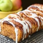 Apple Cinnamon Pull Apart Bread on a sheet rack. Bowl of apples in the background.