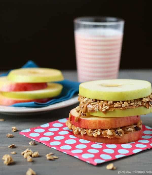 Stack of Apple Sandwiches with Almond Butter and Granola. Glass of milk in background.