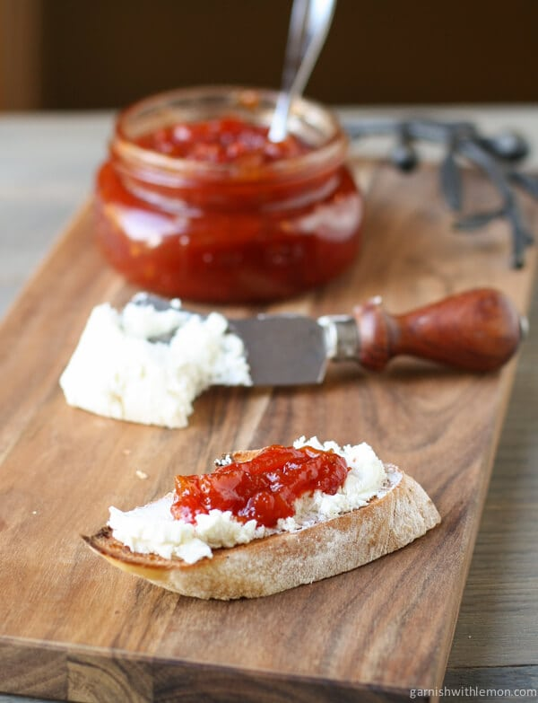 Sweet and tangy tomato jam and goat cheese are slathered on a piece of toasted baguette. A knife with more goat cheese and a jar with tomato jam is on a wooden cutting board in the background.