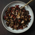 A bowl of wild rice with cranberries and mushrooms.