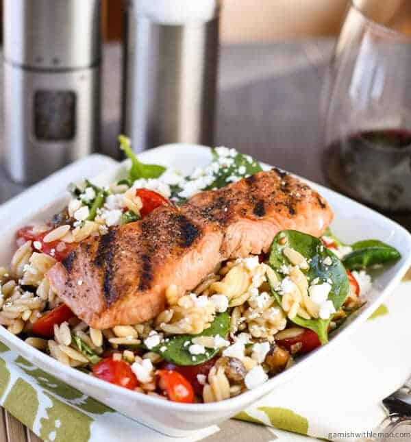 This Salmon with Spinach and Tomato Orzo recipe is one of our family's favorites with heart-healthy salmon on top of a tasty spinach, tomato and orzo salad.