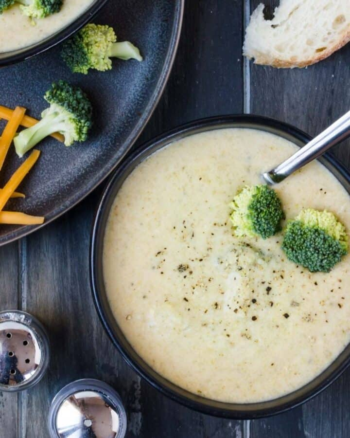 Slow Cooker Broccoli Cheese Soup in a black bowl. Salt and pepper, broccoli, cheese, and bread scattered around the bowl.