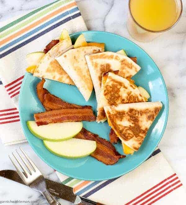 Cheesy Apple Bacon Breakfast Quesadilla on a plate with apples and bacon.
