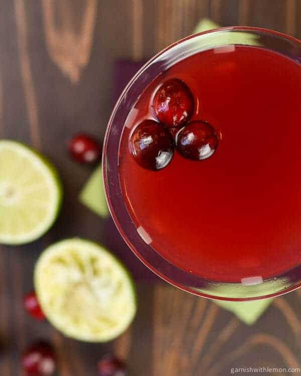 The float of cranberries is a festive touch to this simple Cranberry Gimlet cocktail recipe - the perfect cocktail for all of your fall and holiday entertaining!