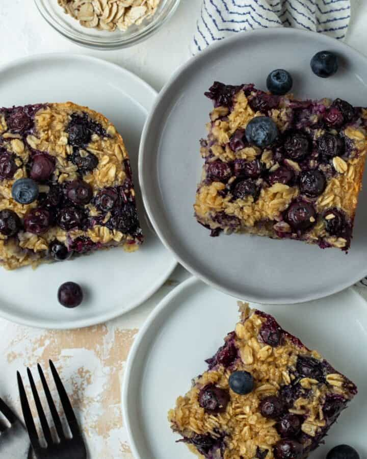 three white plates of blueberry baked oatmeal.