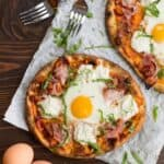 two ham and cheese breakfast pizzas on a dark wood backdrop with forks and eggs on the sides as garnishes.
