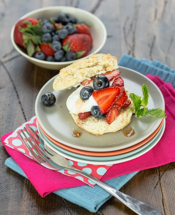 A plate of shortcake with mixed berries and mint.
