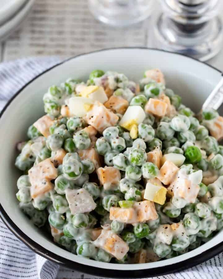 Pea and cheese salad in a white bowl with a fork in the bowl.