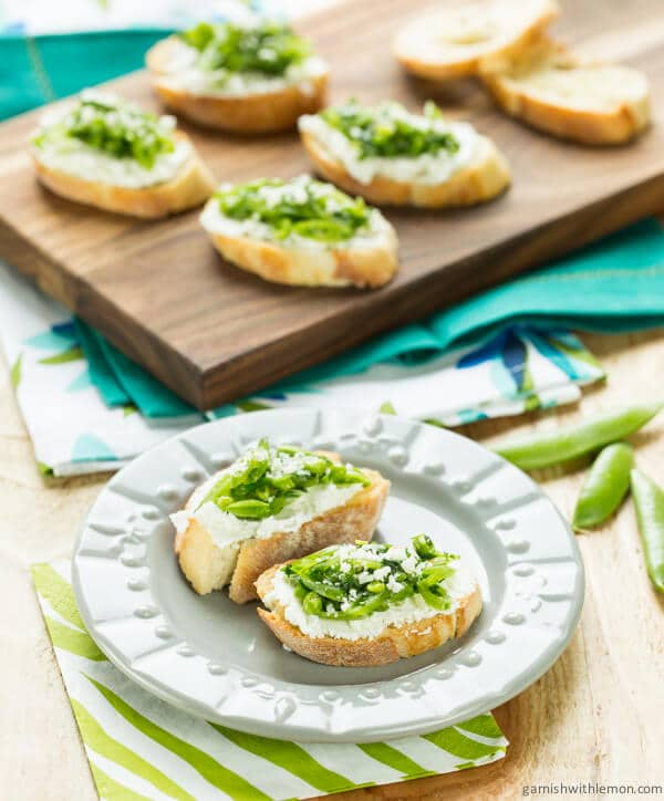 Sugar Snap Pea Crostini with Goat Cheese and Arugula -Welcome all of spring's fresh flavors with this Sugar Snap Pea Crostini with Goat Cheese and Arugula!