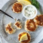 Four mini crab cakes on a silver metal plate with another crab cake cut in half. Lemon garnish and a bowl of sauce.