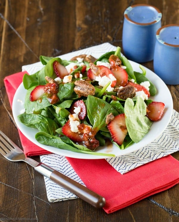 A plate of spinach salad with strawberries on a table.