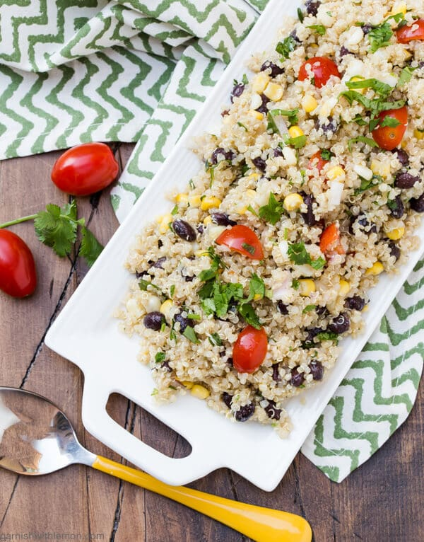 Rectangular white platter filled with Southwestern Quinoa Salad on a green chevron towel. Yellow serving spoon and grape tomatoes on side with sprig of cilantro.