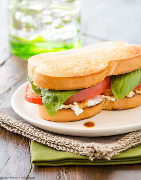 A Tomato and Goat Cheese Sandwich with Balsamic Drizzle on a white plate. Glass of water in background.