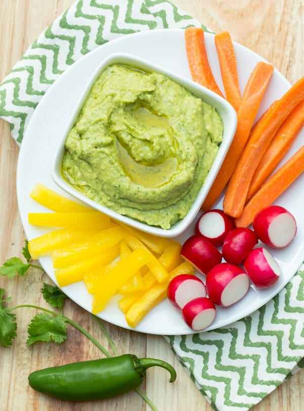 Top down image of Cilantro Jalapeno Hummus on a white platter with vegetables for dipping.