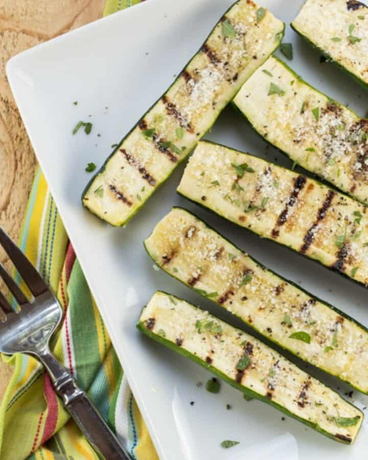 Six grilled zucchini on a white plate sprinkled with parmesan.