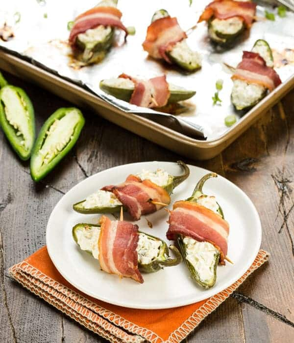 A small white plate of three Apple Bacon Jalapeno Poppers with a sheet pan of poppers in the background. Halved jalapeno peppers are stuffed with a cream cheese, apple and green onion mixture, wrapped with bacon and baked.