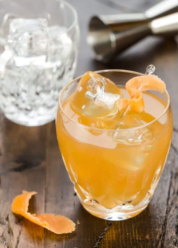 maple old fashioned in low ball lasses with orange peel.