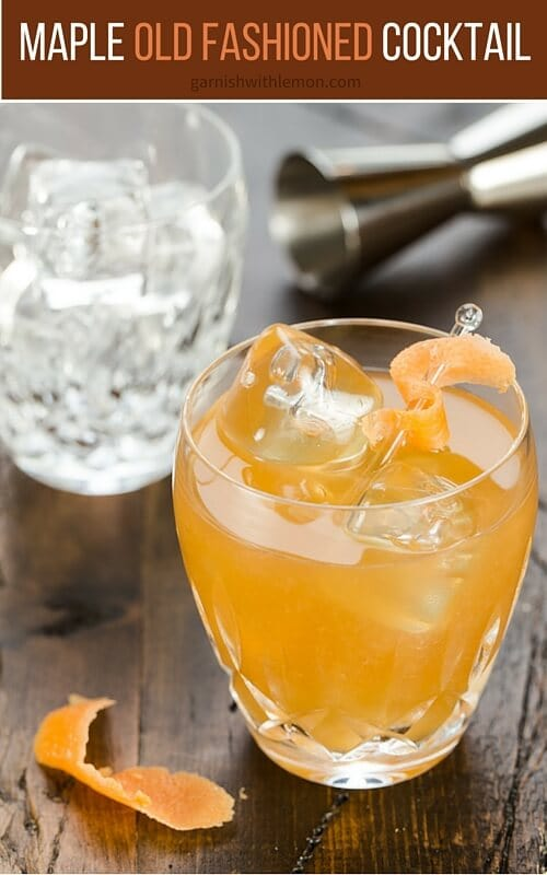 A glass of Old fashioned with ice and orange peel.