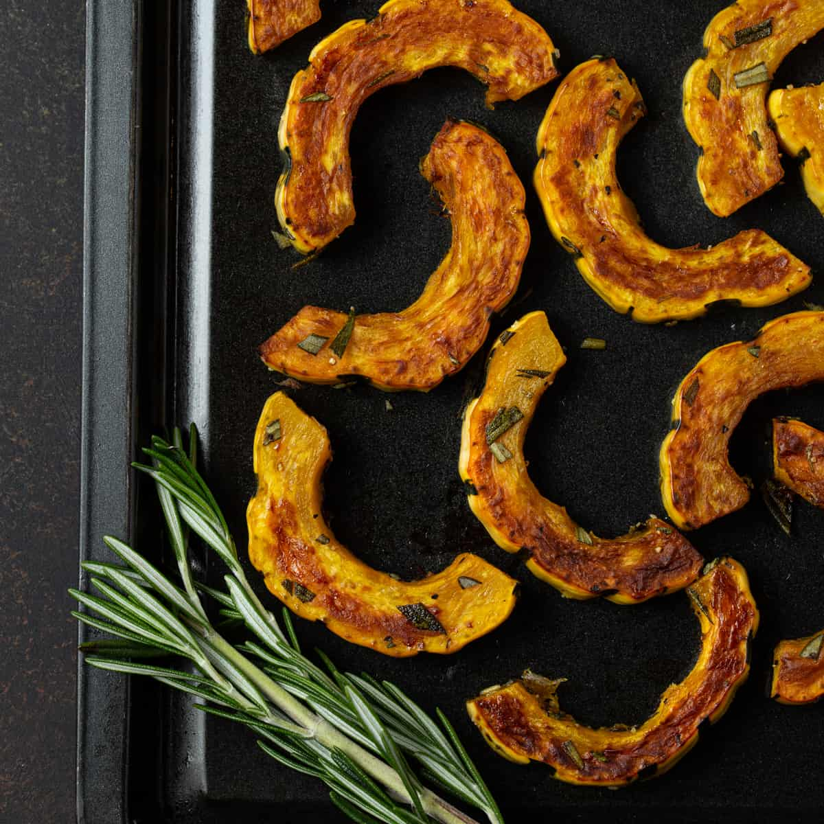 sliced squash on sheet pa, with rosemary.