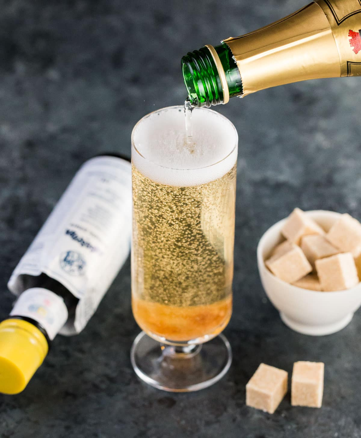 Champagne poured into a flute glass with a bowl of brown sugar cubes and a bottle of bitters for a Classic Champagne Cocktail.