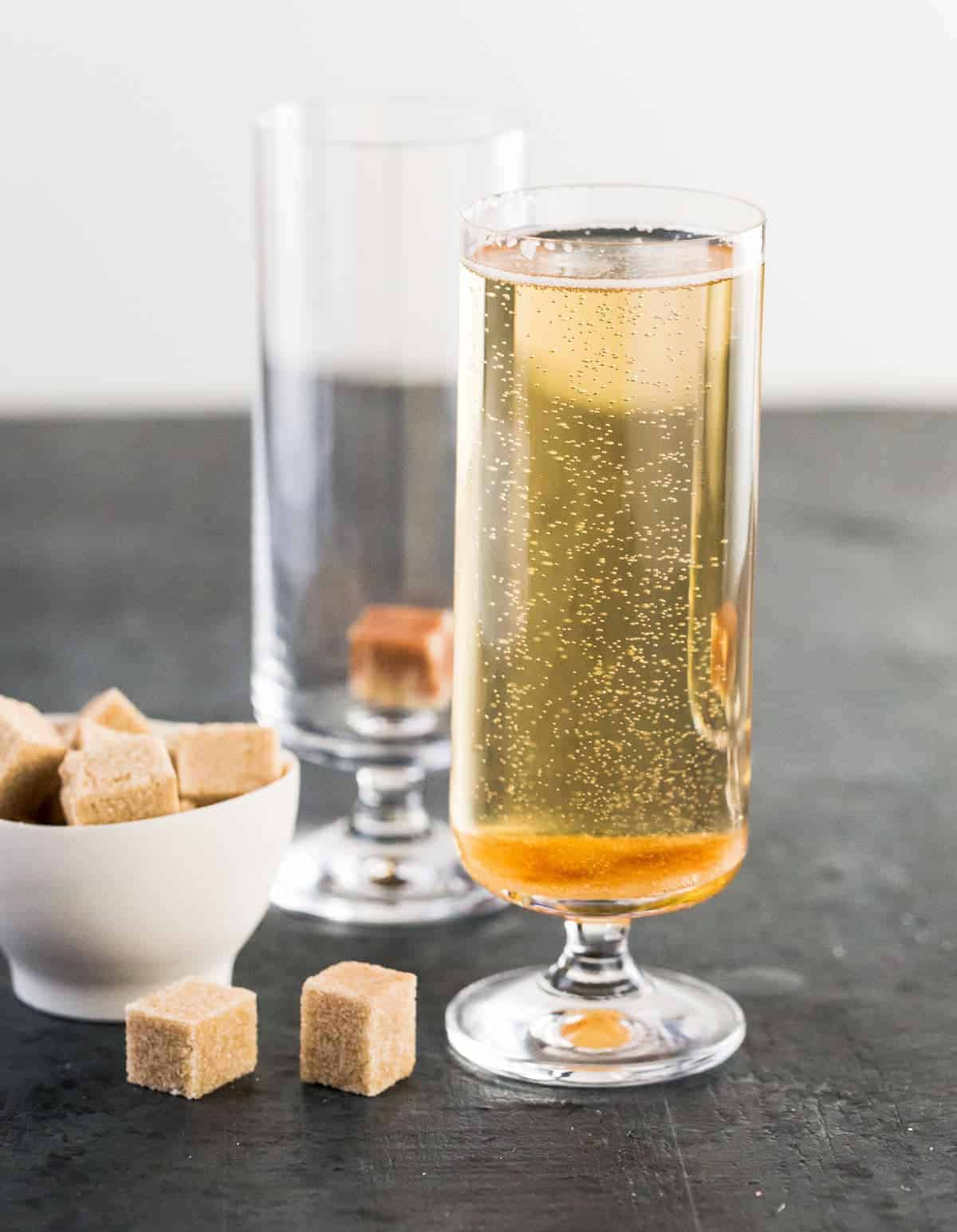 Straight on image of Classic Champagne Cocktail with brown sugar cubes for garnish.