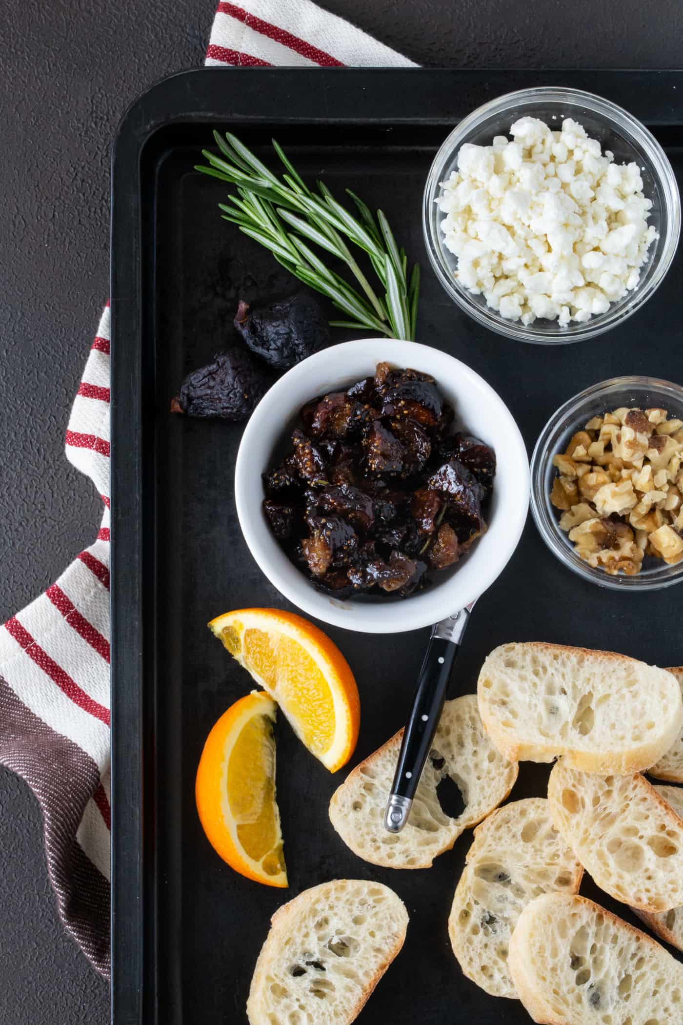 Ingredients for Fig and Goat Cheese Bruschetta on a sheet pan, including black mission figs, walnuts, goat cheese, oranges, baguette slices and fresh rosemary.