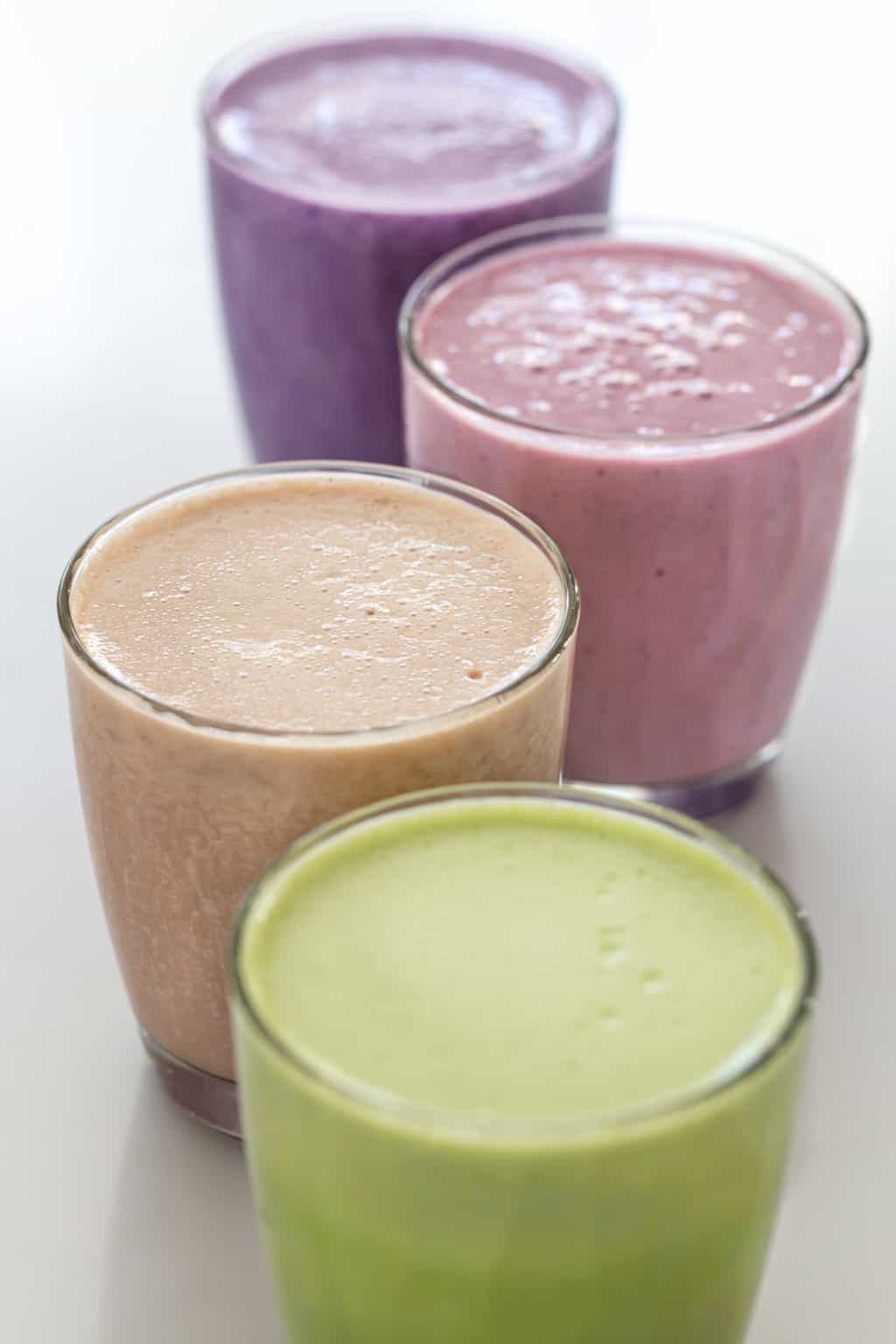 Four glasses filled with colorful smoothies.