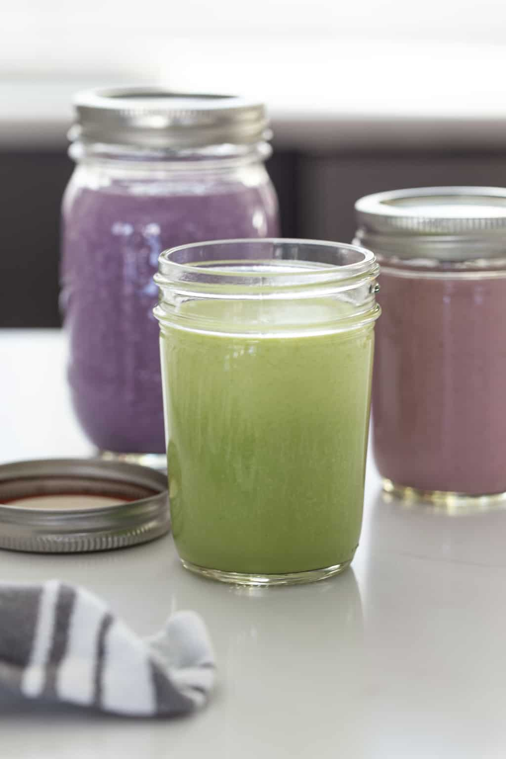 Mason jars filled with healthy smoothies that can be made in advance and frozen.