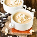 two bowls of beer cheese soup on burlap with popcorn.