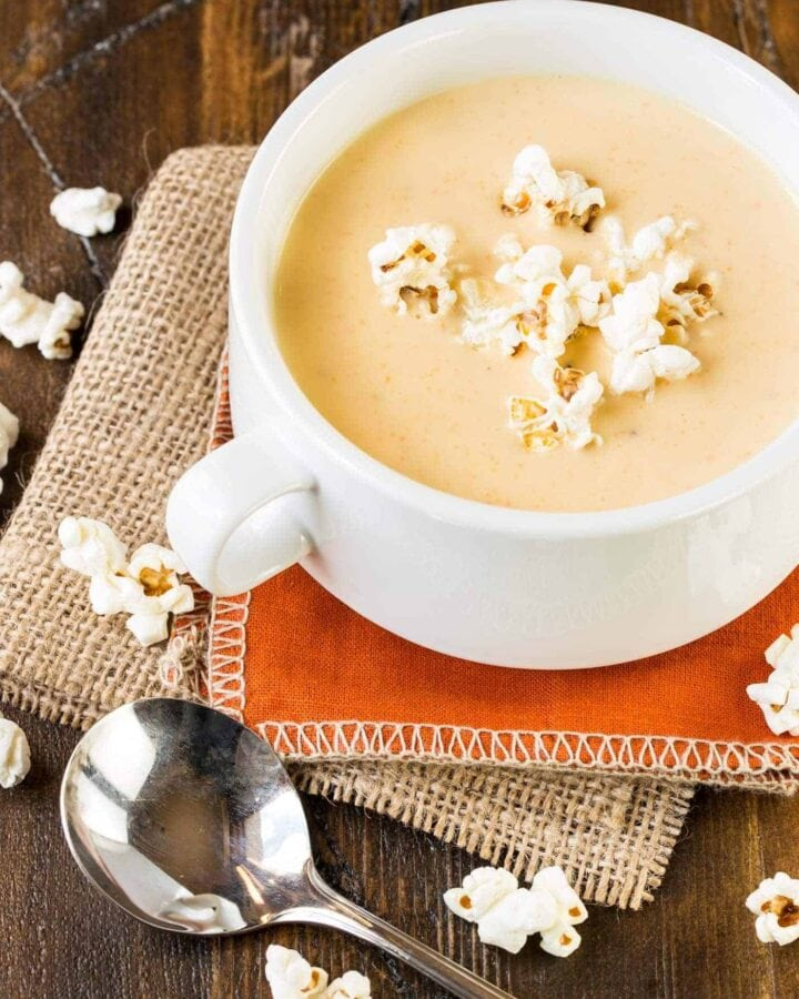A cup of beer cheese soup on a table.