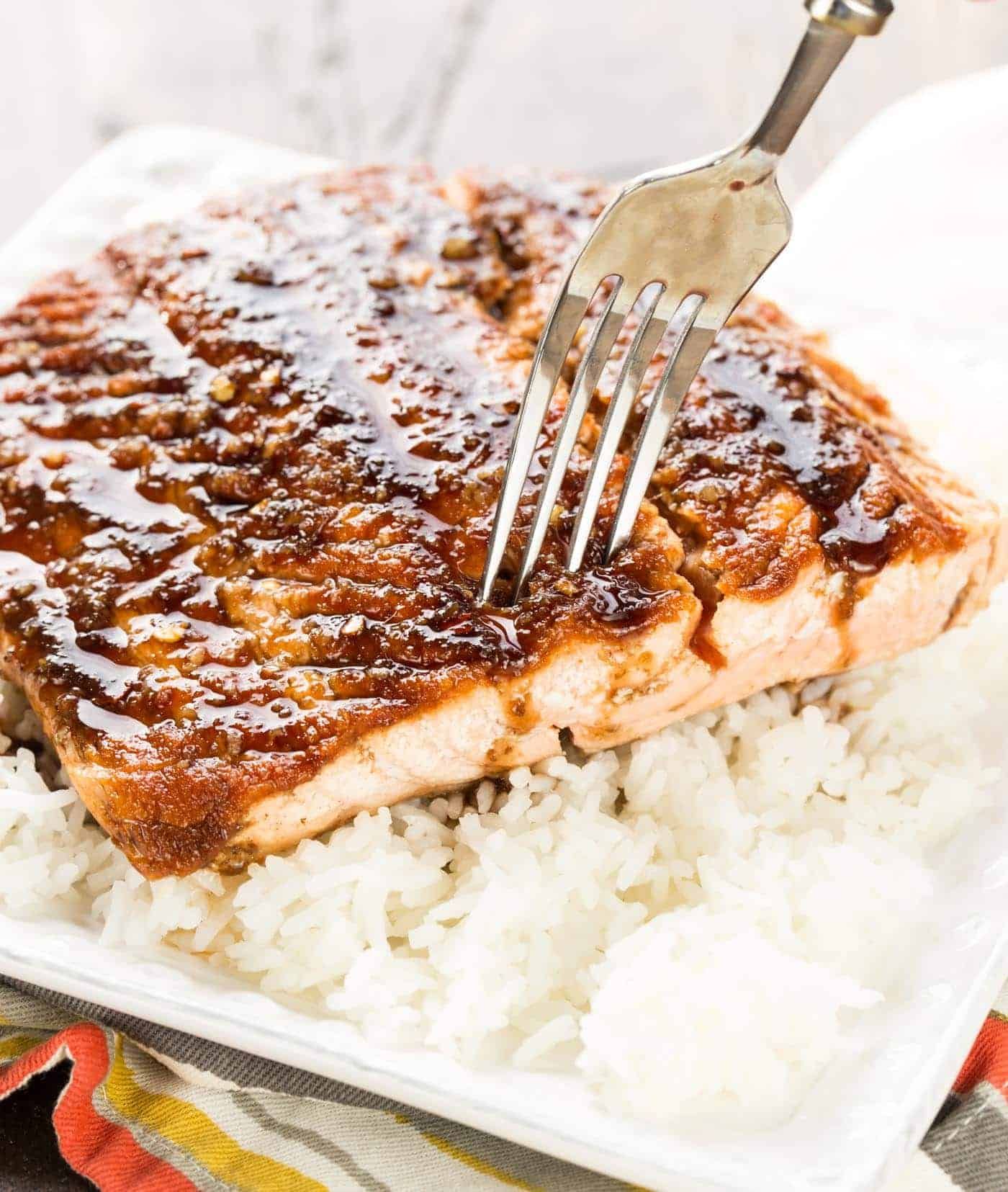close up of salmon on a plate with rice.