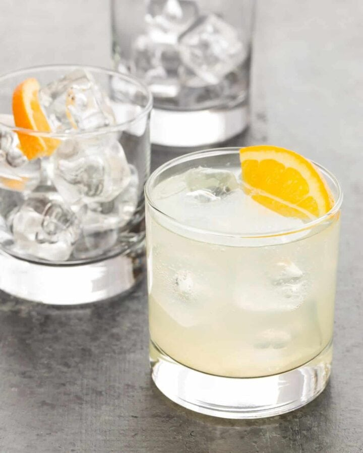 Glass cup filled with citrus gin soda with orange wedges.