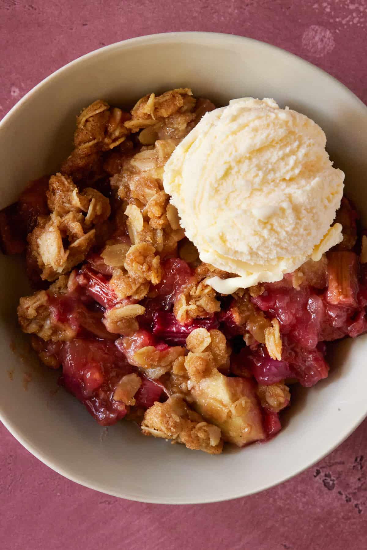 Bowl of fruit crisp with ice cream.
