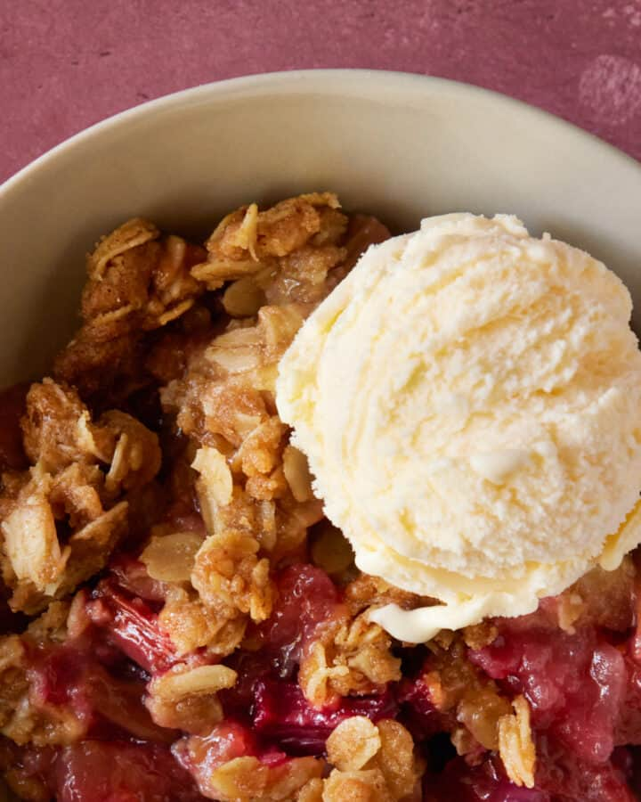 bowl filled with fruit crisp and vanilla ice cream.