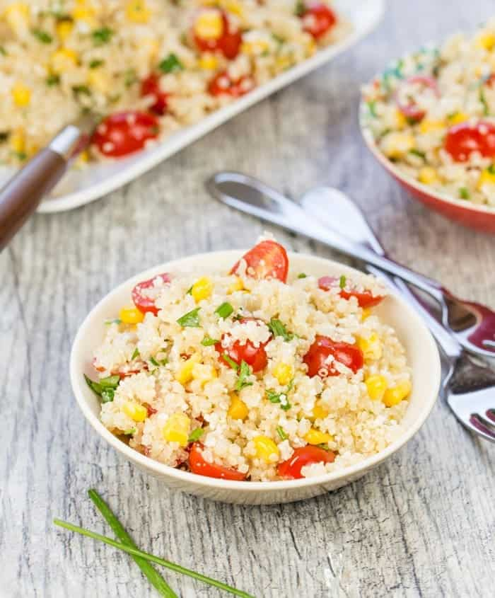 Small bowl of quinoa salad with cotija cheese, corn and tomatoes in foreground with additional small bowl in the background. Large plate of quinoa salad in back with brown handled spoon for serving. Chives in front of small bowl in front all on a gray tile background.
