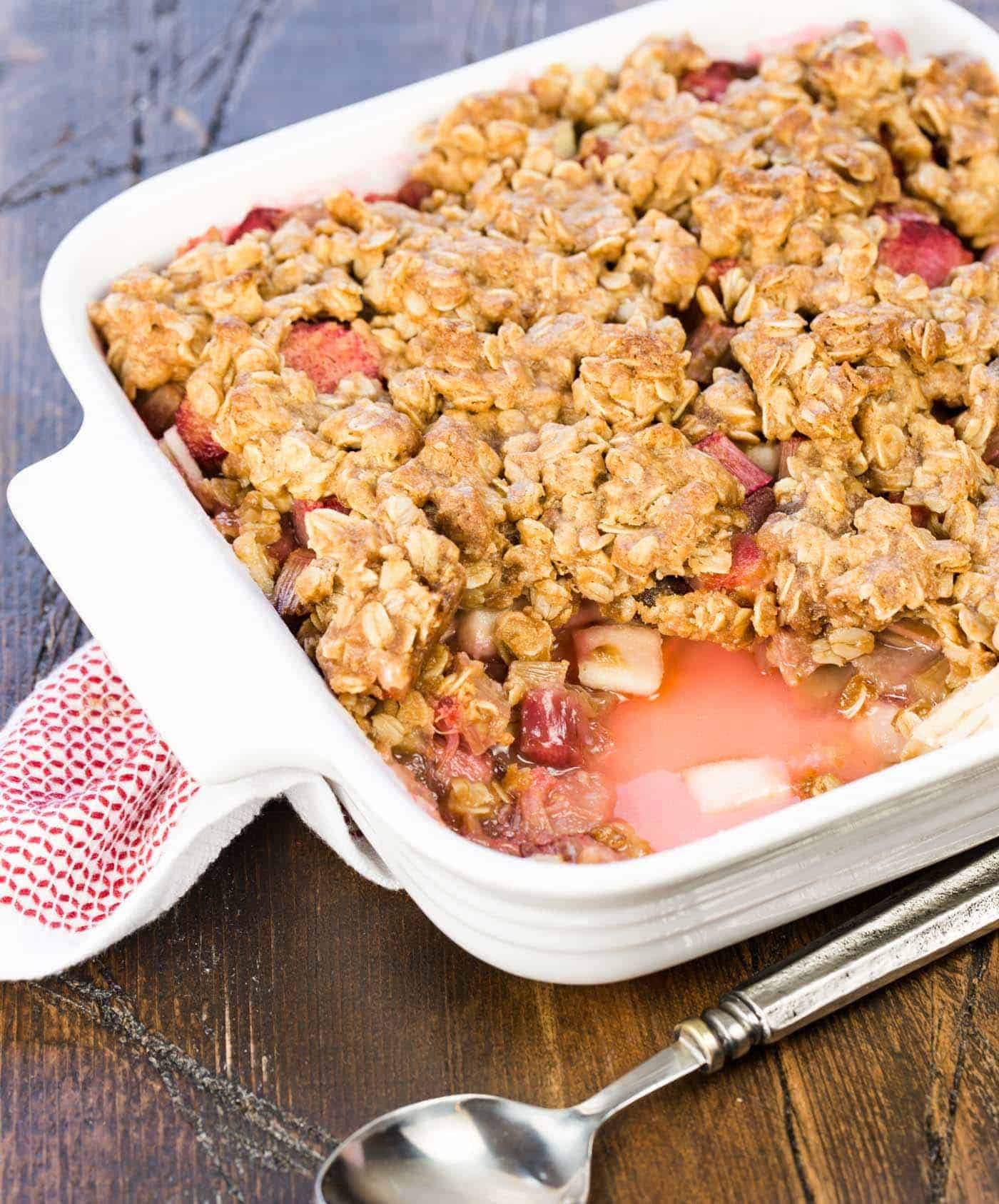 Close up of rhubarb crisp in white pan.