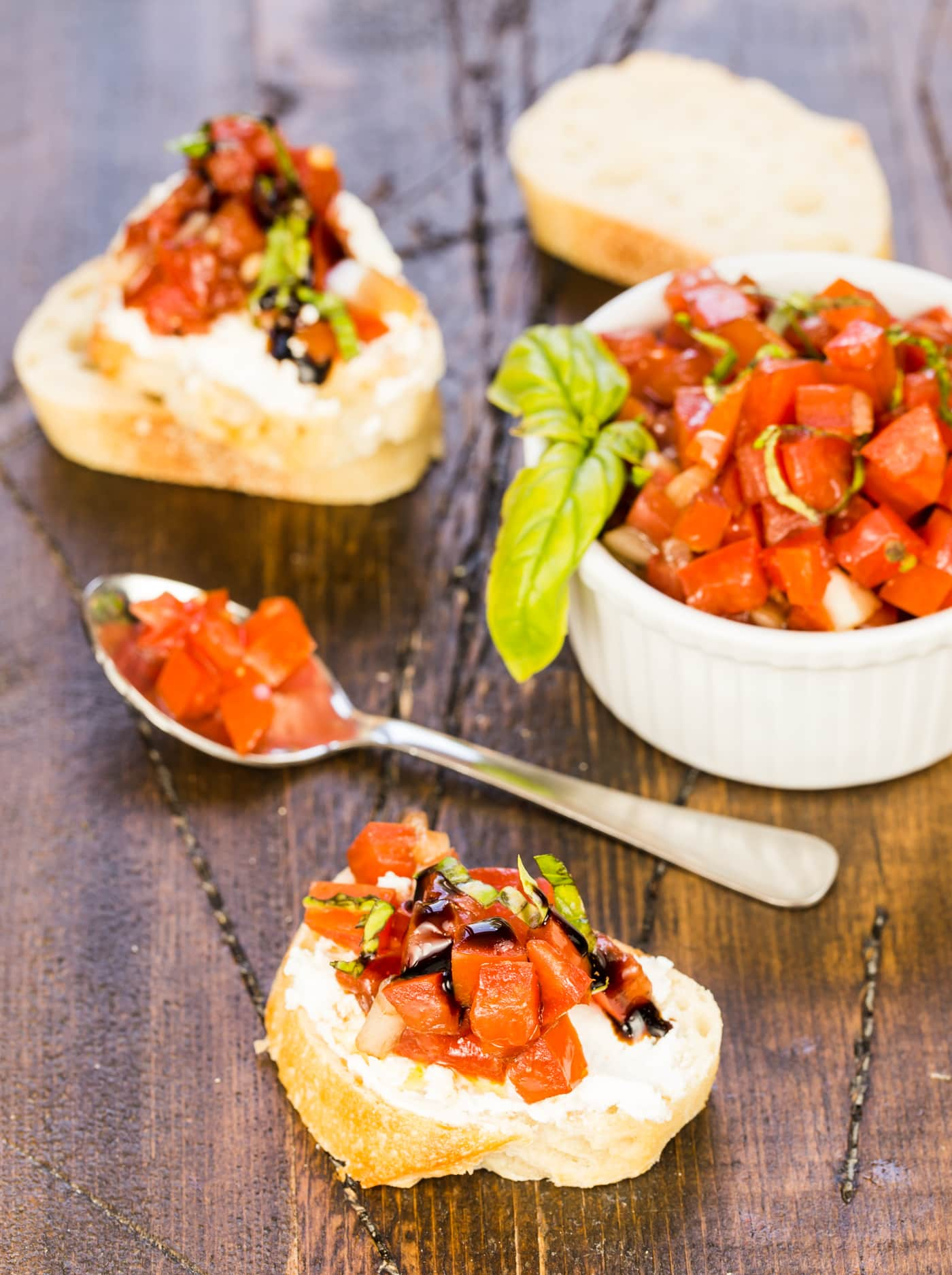 Balsamic bruschetta in white ramekin on dark board with slices of crostini spread with ricotta cheese and topped with bruschetta. Basil leaves on table as well as small spoon filled with bruschetta.