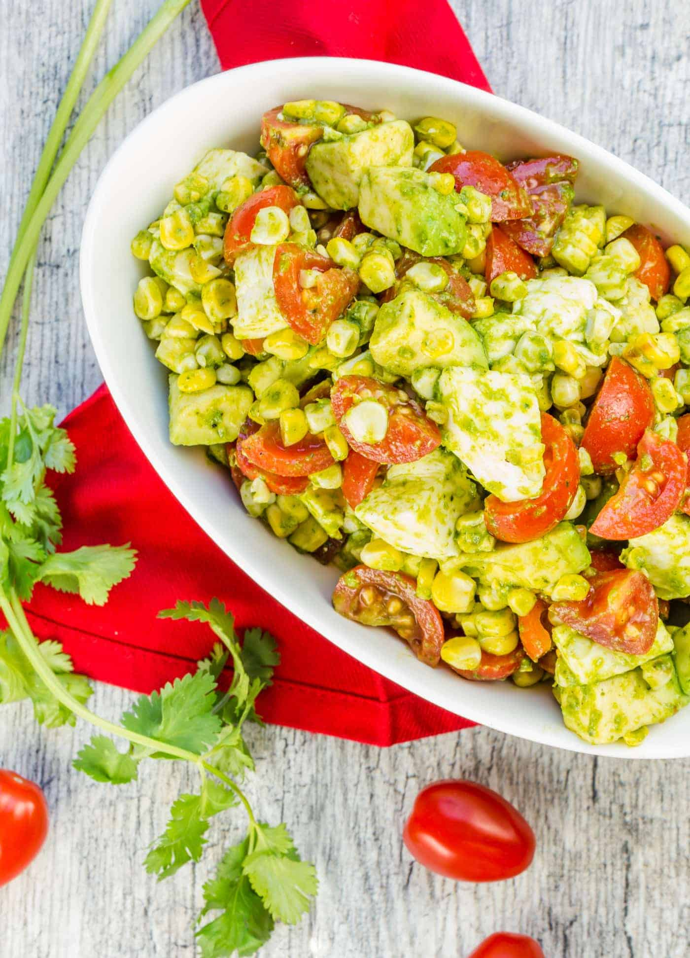 White bowl of sliced tomatoes, grilled corn kernels, avocado cubes and fresh mozzarella in a cilantro lime dressing.