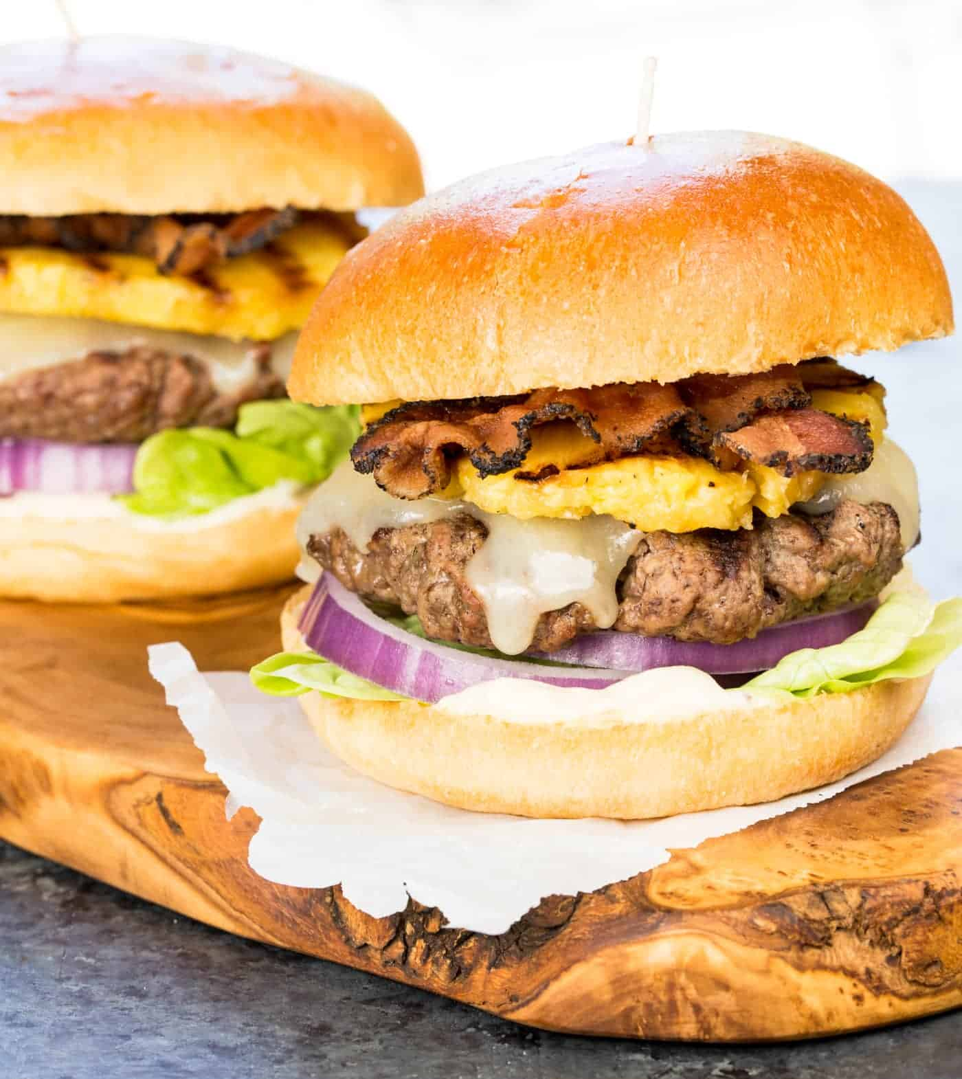 Image of two Sweet and Spicy Hawaiian Burgers on a wooden cutting board.