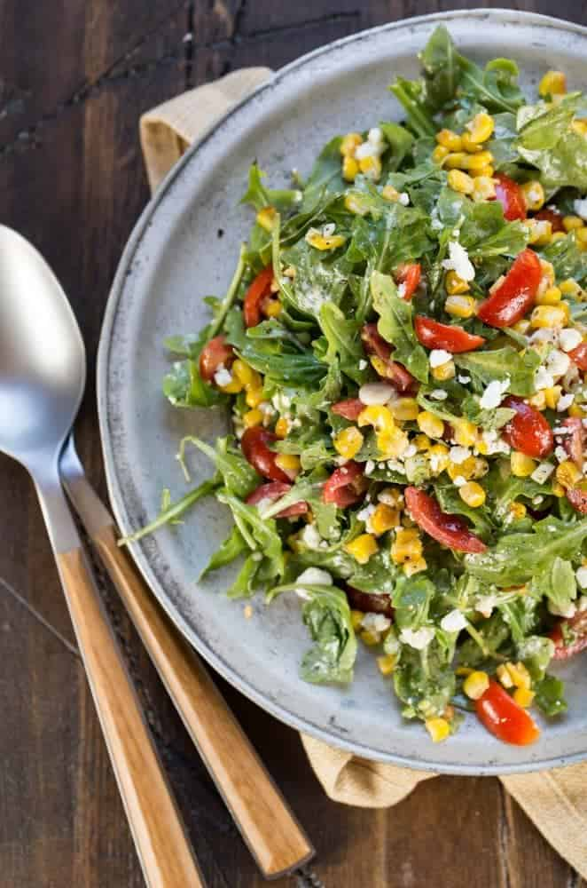 Silver plate with mounded Arugula, Goat Cheese, Corn and Tomato Salad on a dark background with gold linen.