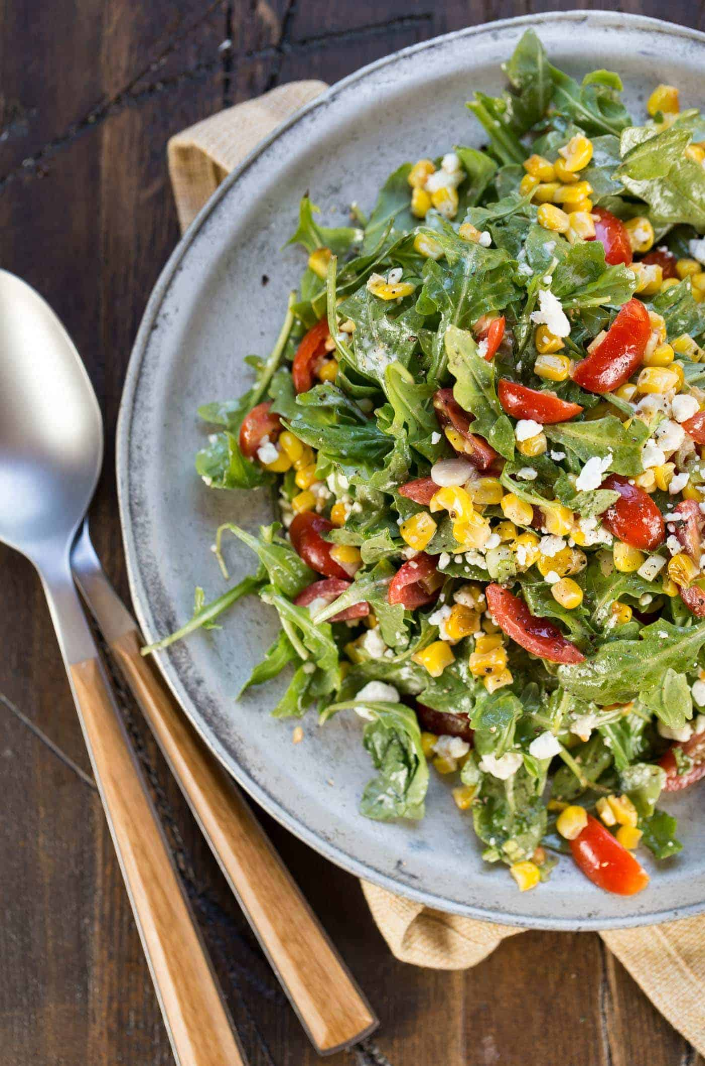 A silver plate mounded with Arugula Corn Goat Cheese Salad.