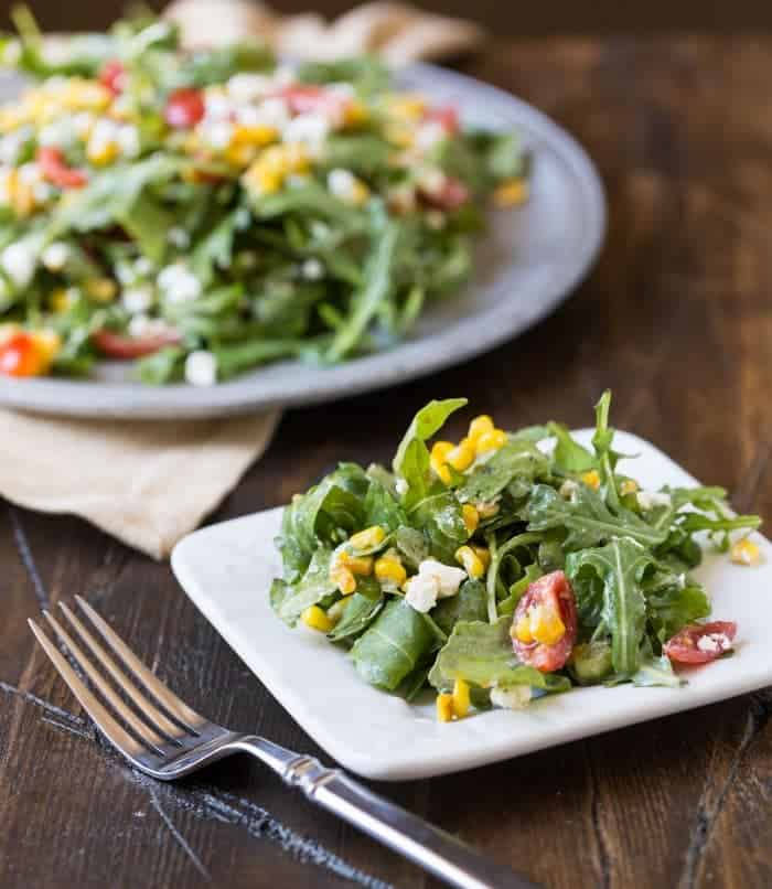 Small white plate of Arugula, Goat Cheese and Corn Salad in foreground with larger silver plate of salad in background.