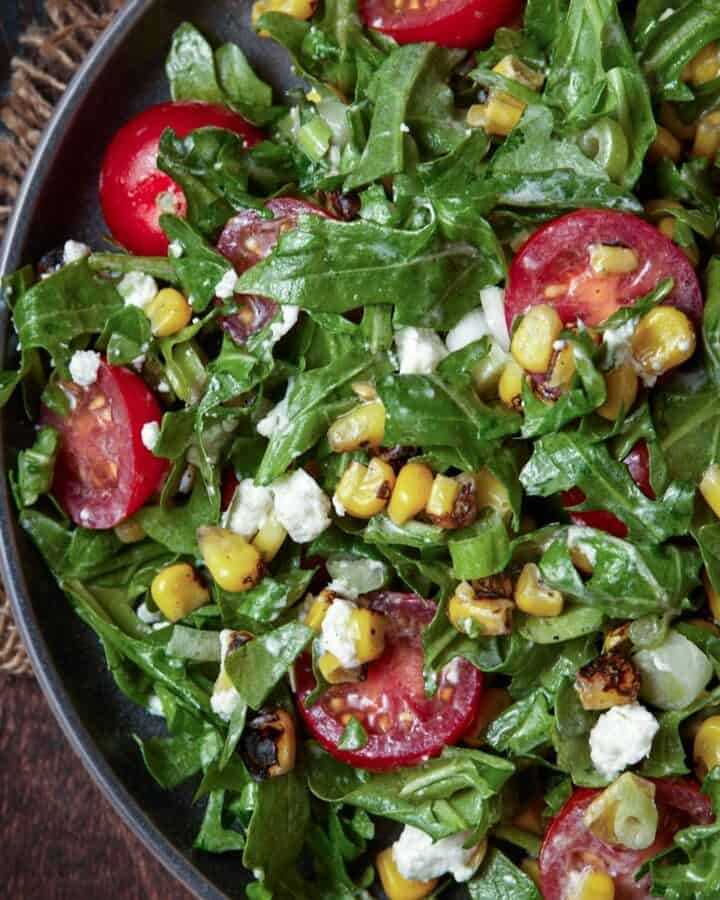 arugula salad on plate with corn and tomatoes.